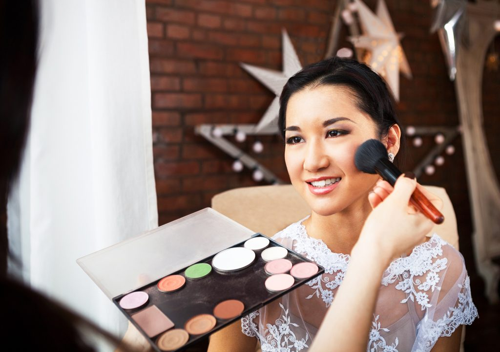 make-up artist doing makeup for young beautiful bride