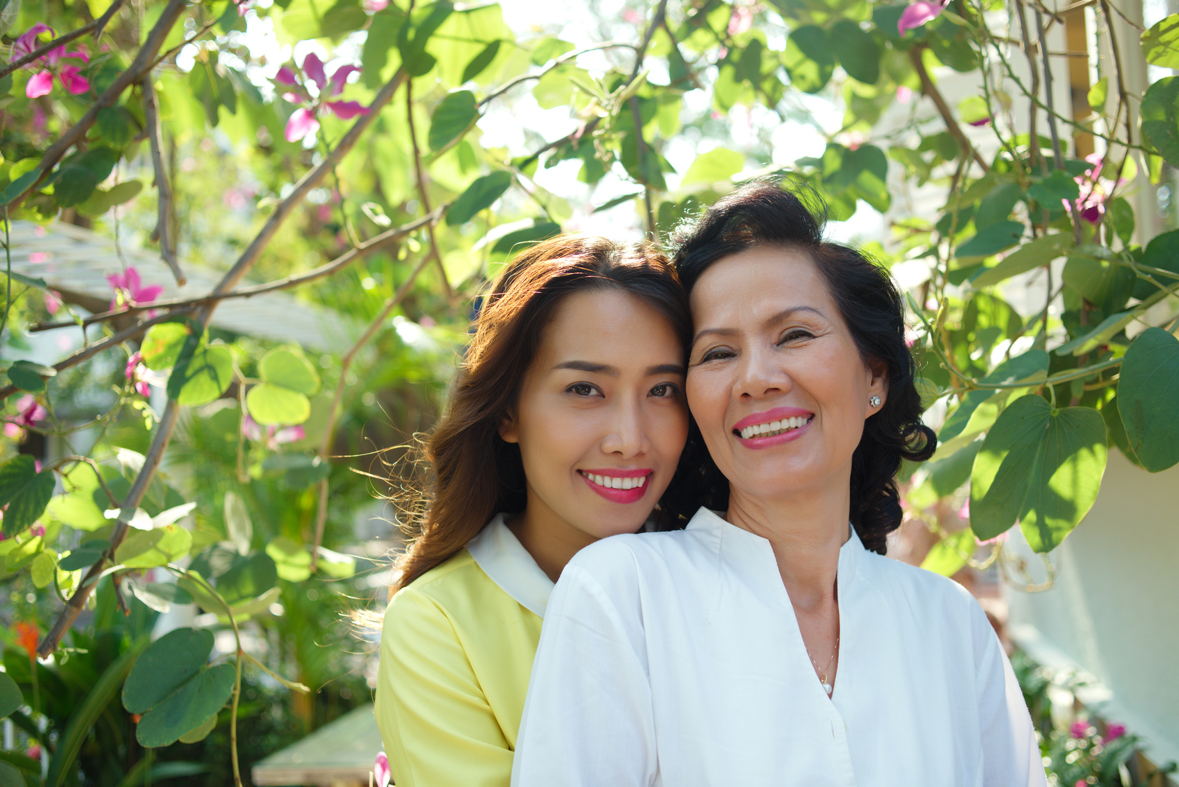 Portrait of happy Vietnamese mother and daughter in the garden