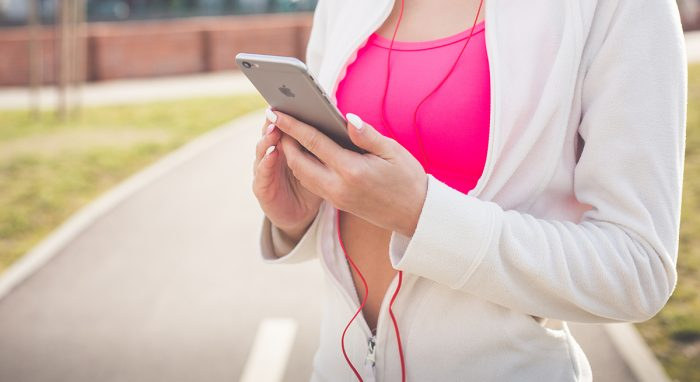 fitness girl listening to music on iphone