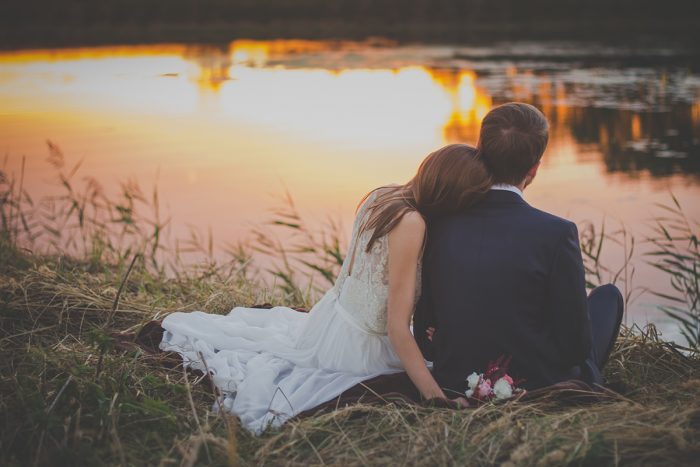 bridal couple sitting by the lake