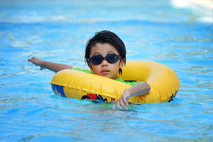 Asian boy in tube learning to swim