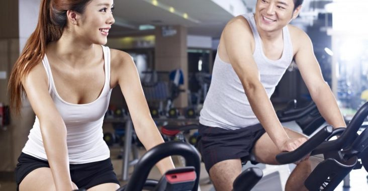 asian-man-and-woman-exercising-on-bike