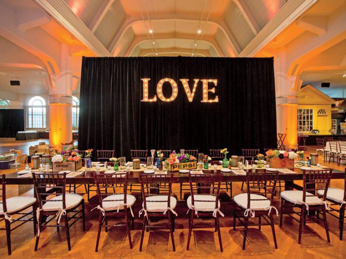 wedding reception in a hall with a love sign