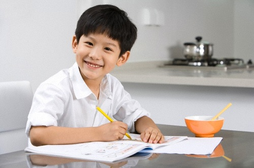 Young boy doing homework in kitchen --- Image by © Blue Jean Images/Corbis