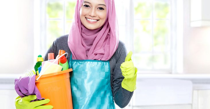 portrait of housewife wearing hijab holding bucket full of cleaning supplies and giving thumbs up with copy space