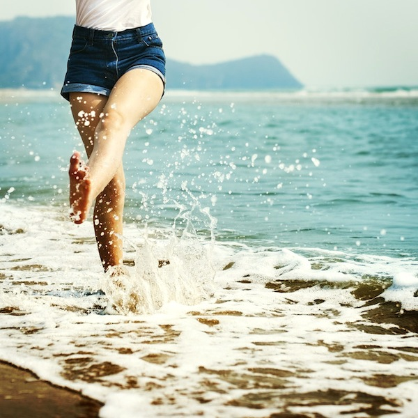 woman playfully kicking water on the shore