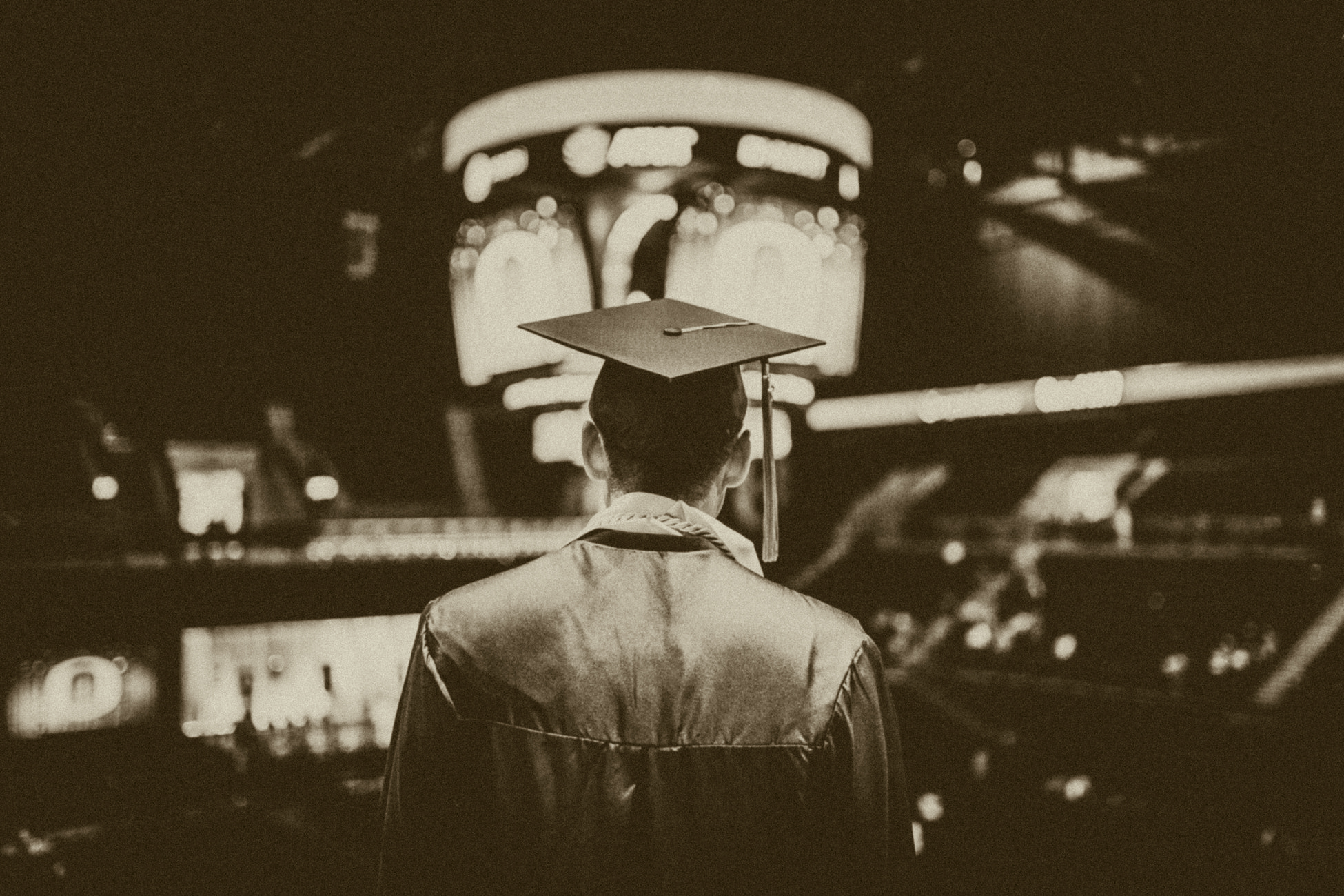 black and white photo. guy in graduation cap and toga facing a stadium