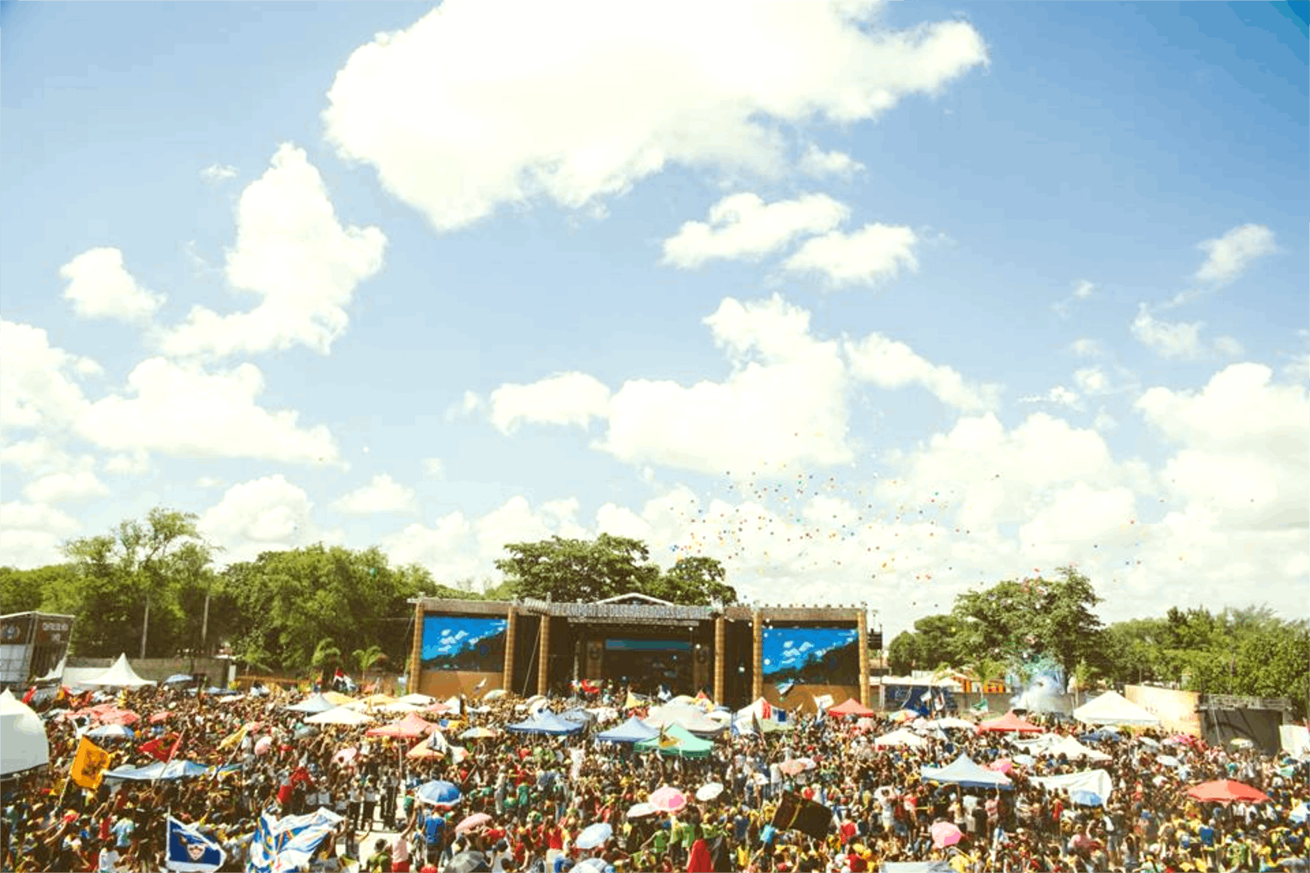 A concert stage on a huge field filled with thousands of people
