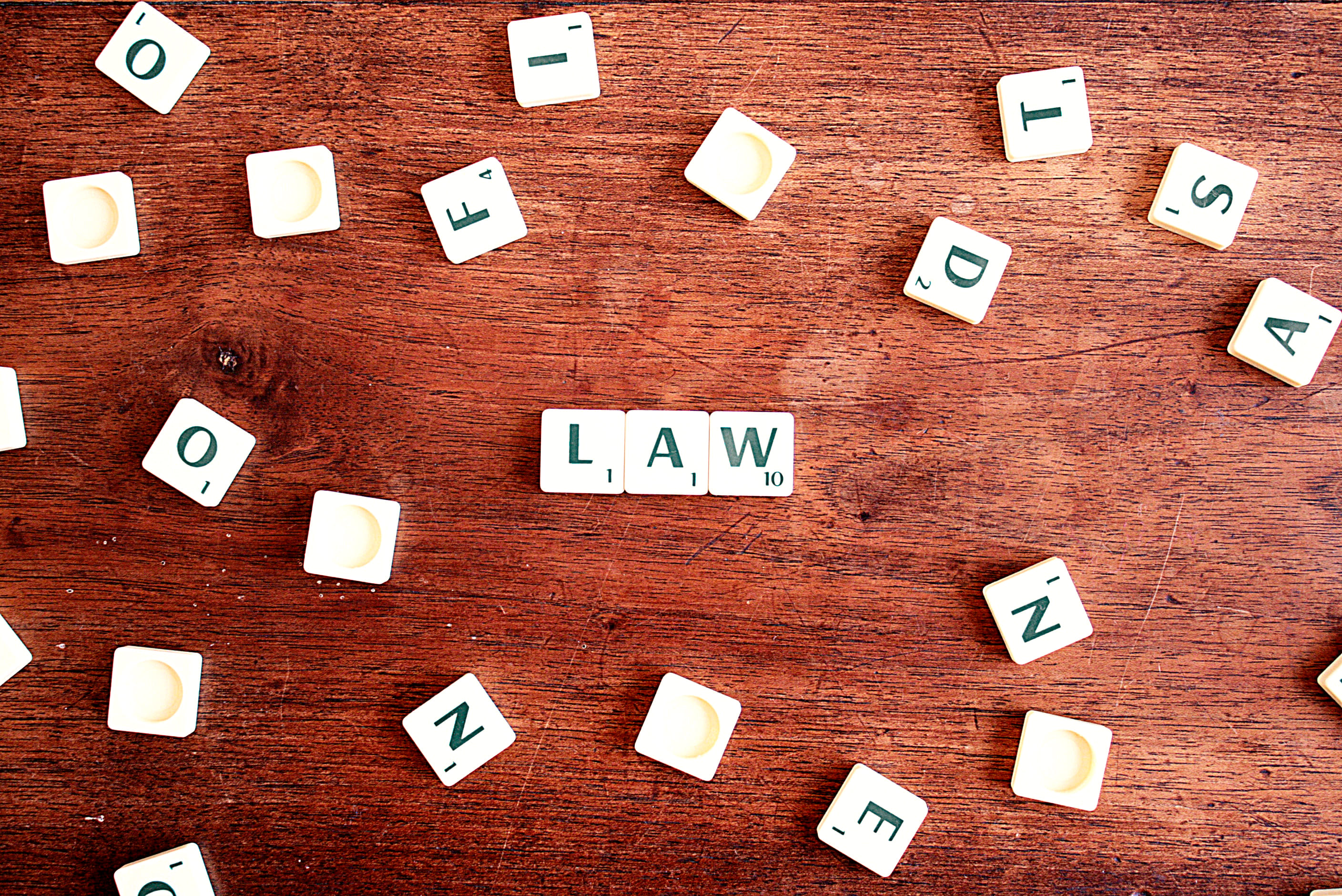 "scrabble pieces scatter on a wooden table, with the word ""law"" spelled out in the middle"
