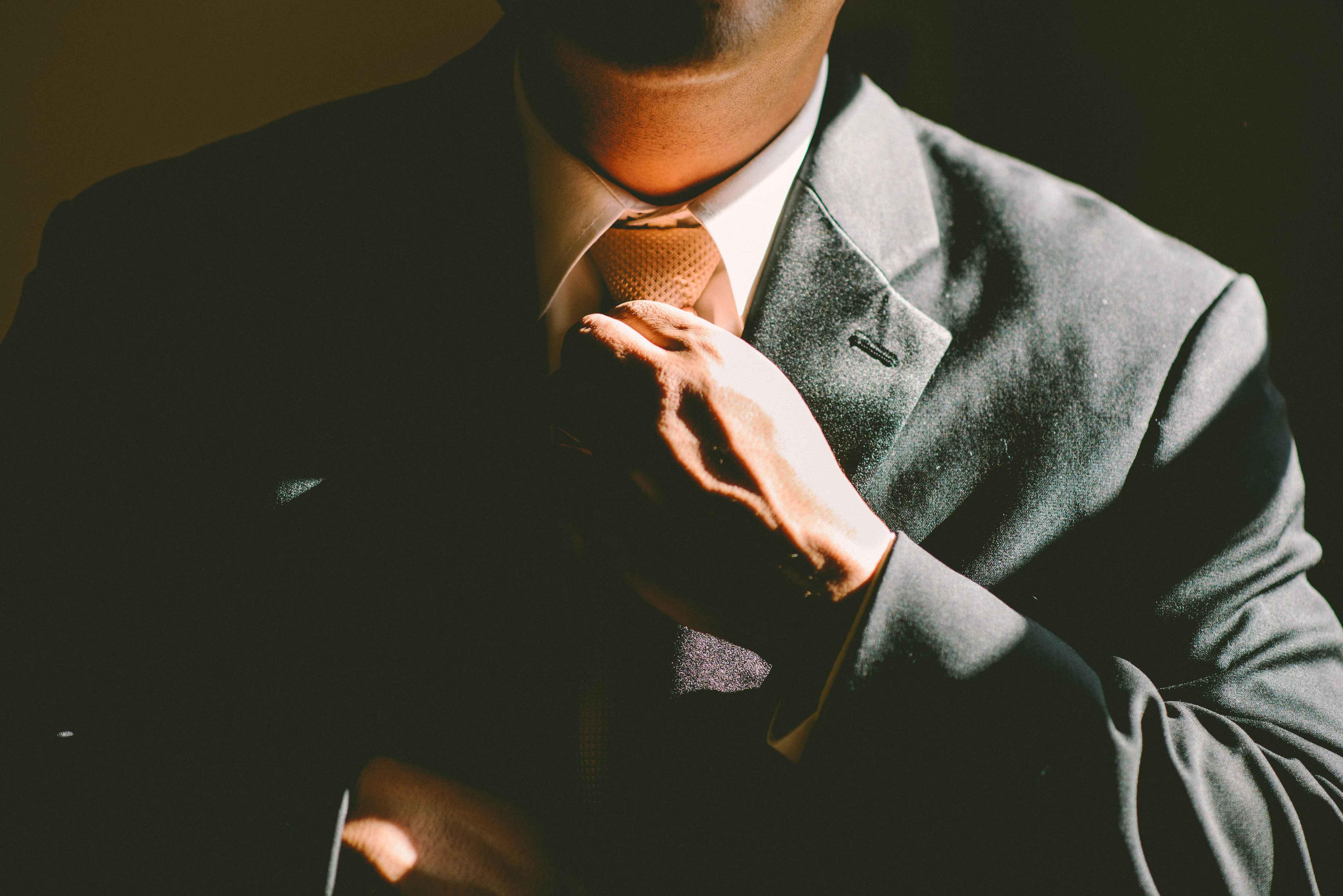 Man in black suit fixing his tie