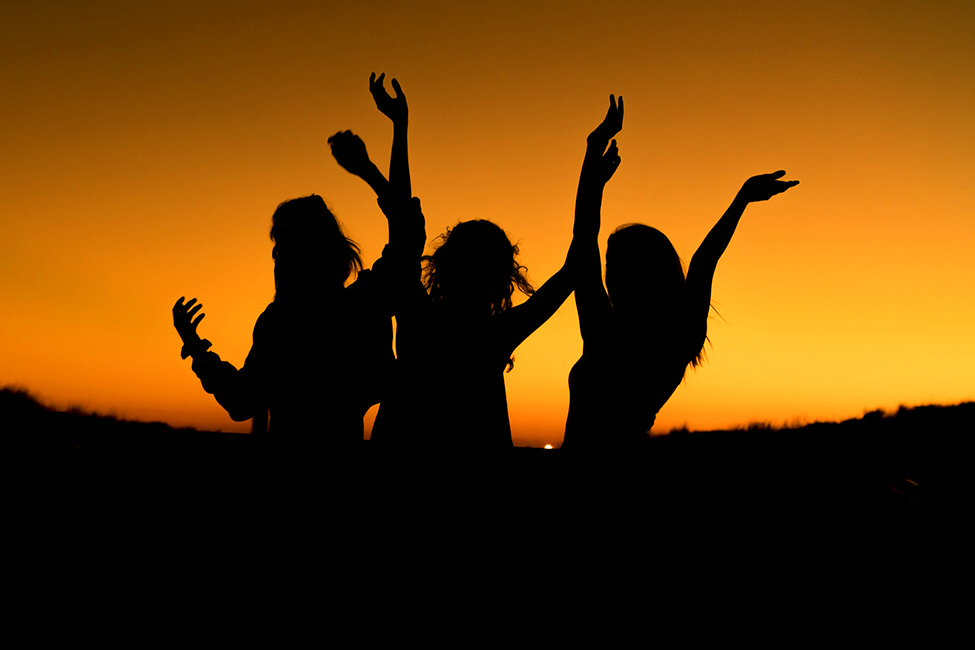 Silohoutte of three people waving their hands in sunset background