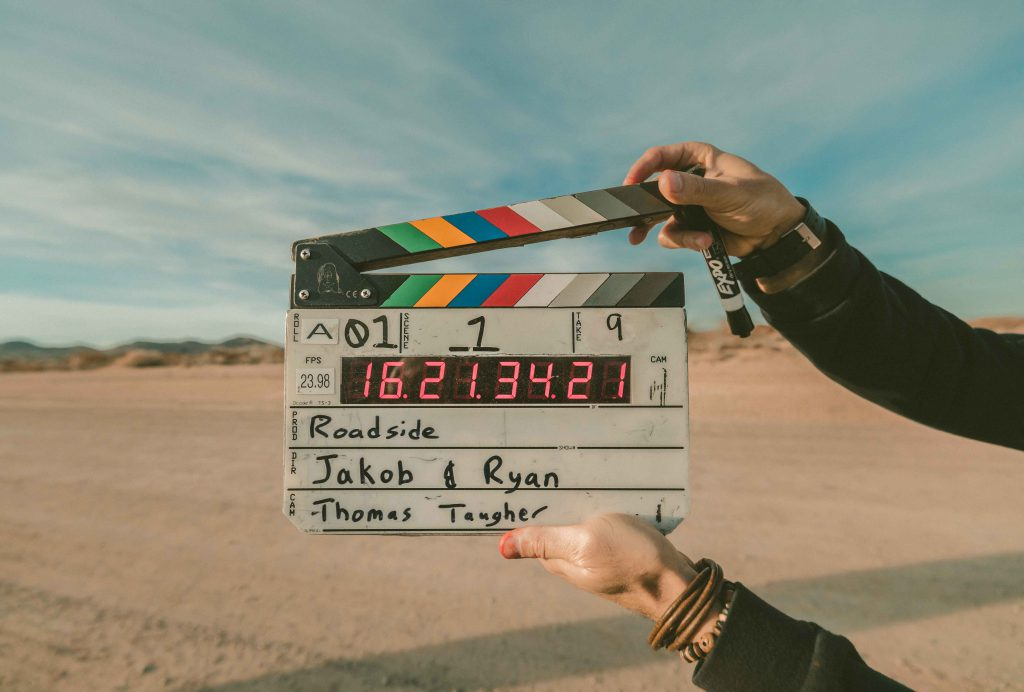 a pair of hands holding up a clapperboard against a desert scenery and blue sky