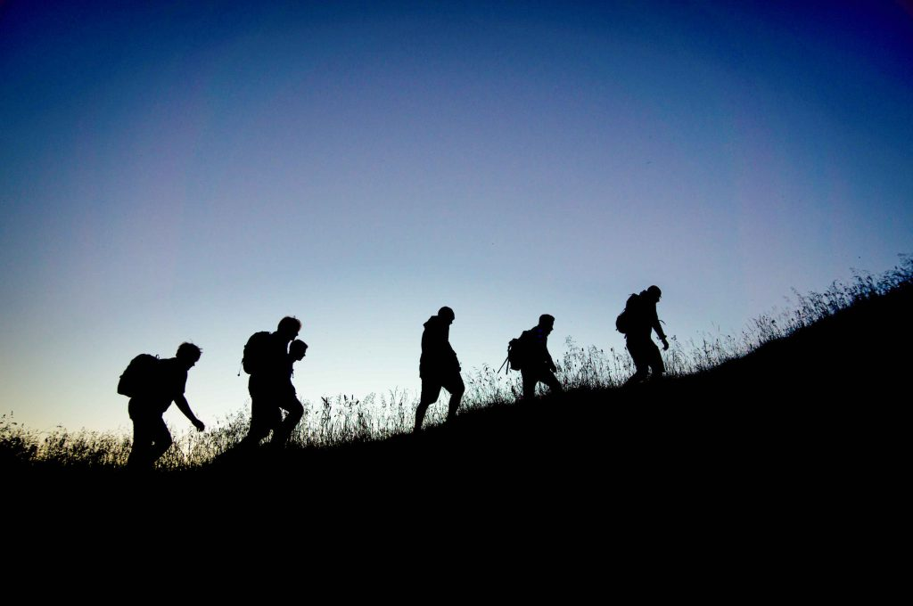 silhouette of 5 hikers climbing a low grassy hill