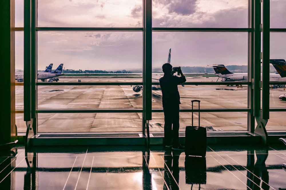 silhouette of man standing beside his luggage in front of huge airport window. he takes a photo of airplanes parked on the runway