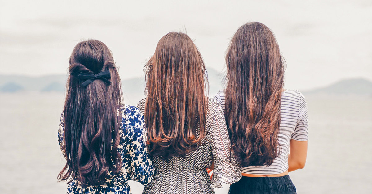 back view of three long-haired women