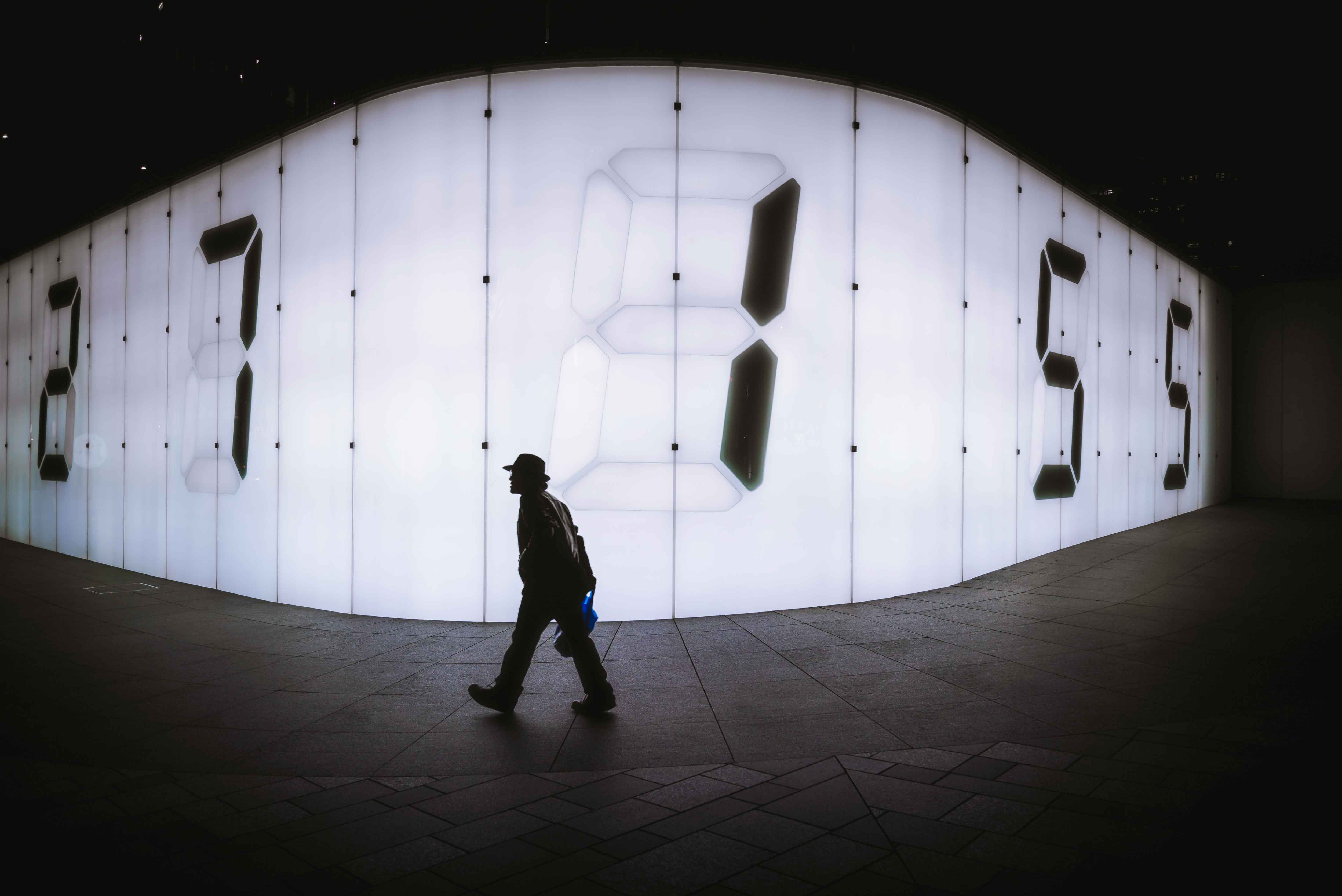 silhouette of man walking in front of an illuminated wall with huge numbers