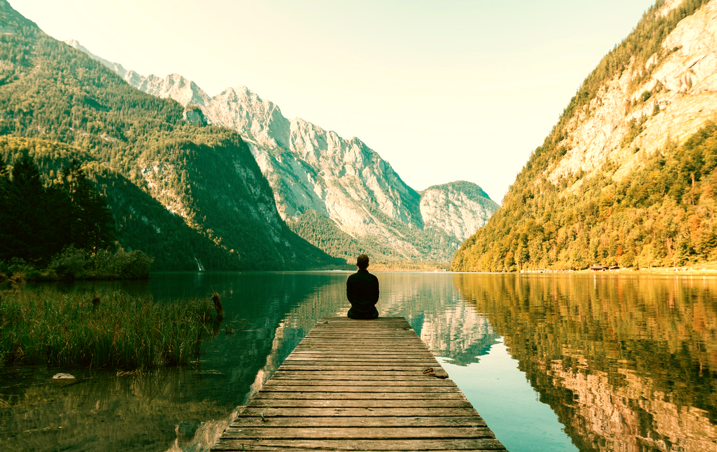 A man sitting on the end of a dock facing a lake and mountains