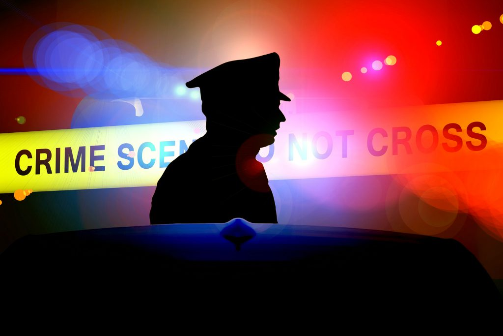 Silhouette of police officer standing in front of a crime scene barricade tape