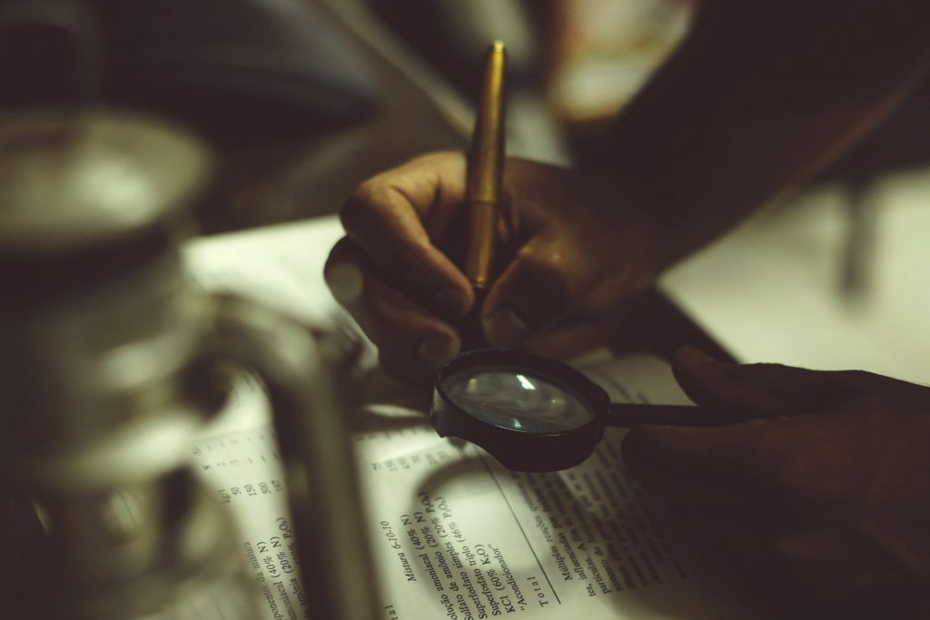 Hand holding a pen and magnifying glass on top of a book