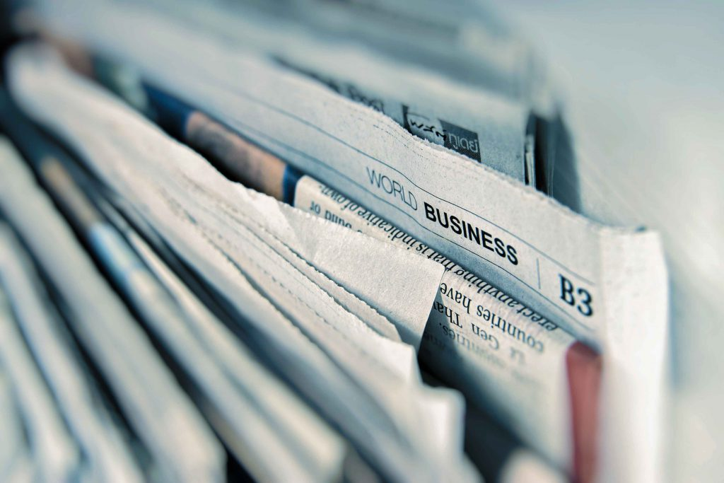 "newspapers neatly compiled together, one newspaper is labelled ""Business"""