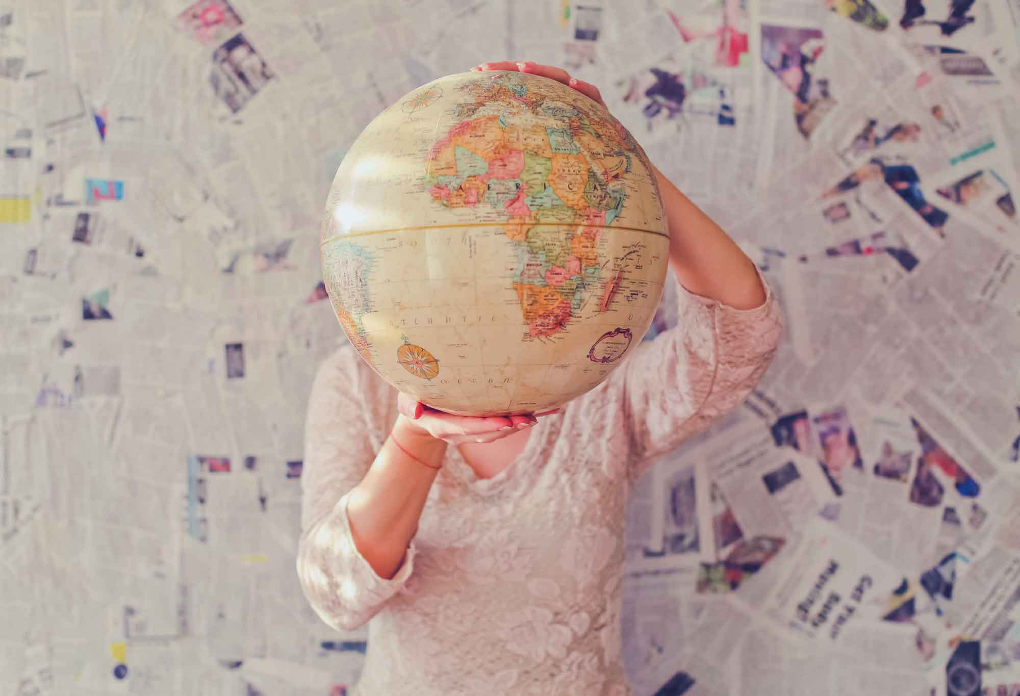 girl holding up a huge globe, covering her face. newspapers fill up the wall behind her
