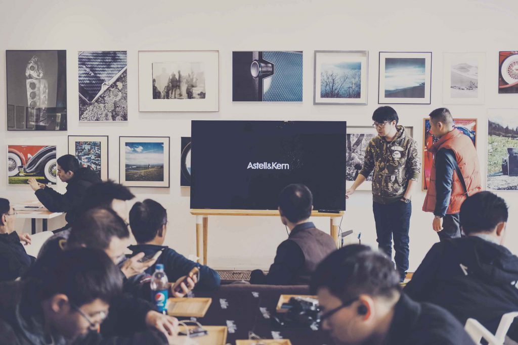 two men making a presentation on a huge flatscreen television in front of a group. nice framed photographs hang on the wall behind the presentors
