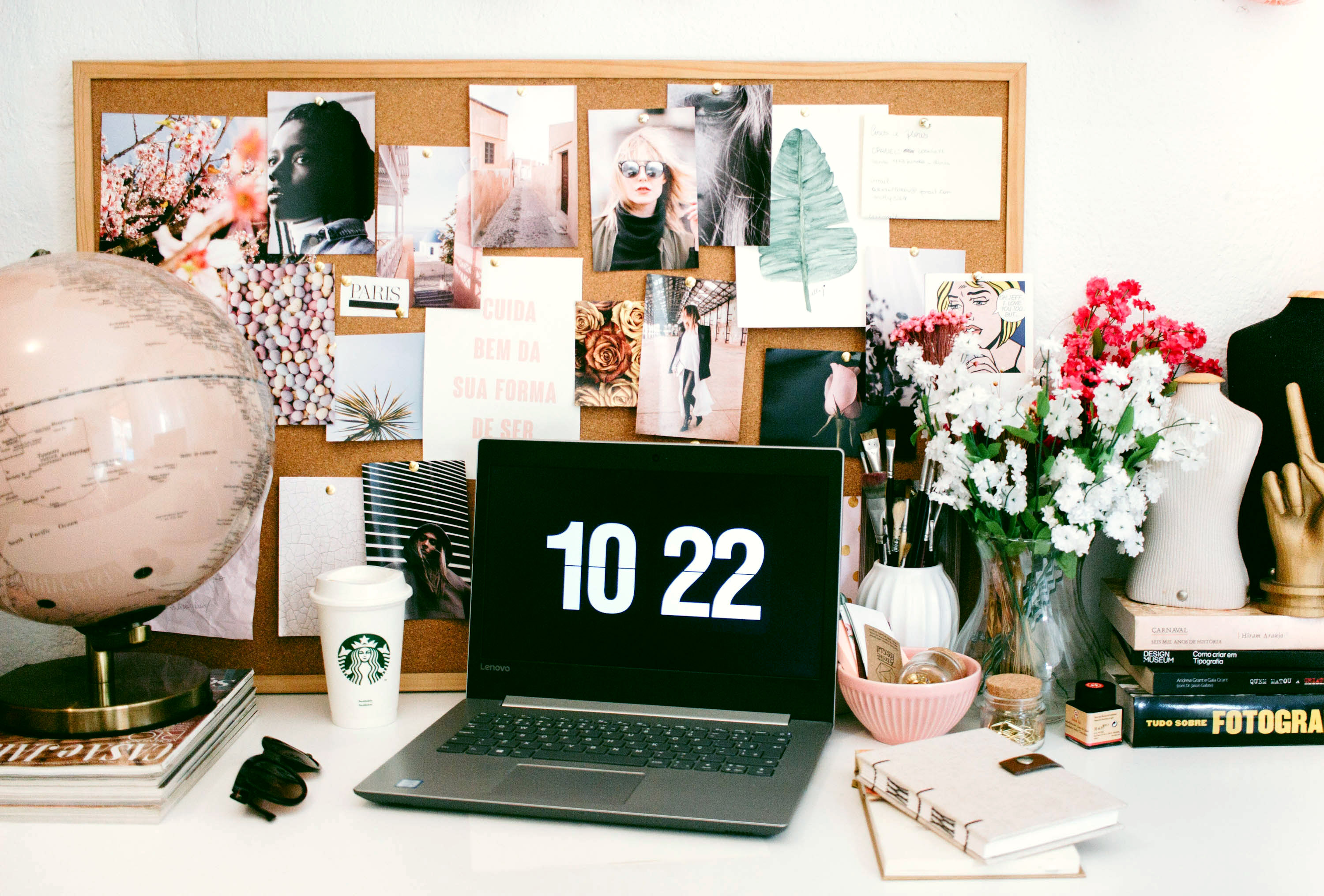 Laptop on a busy desk. Cork board filled with nice photographs on the wall