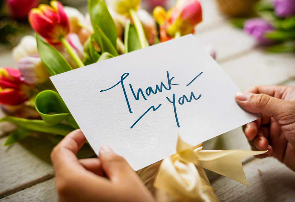 "hands holding a ""thank you"" card over a bouquet of flowers"