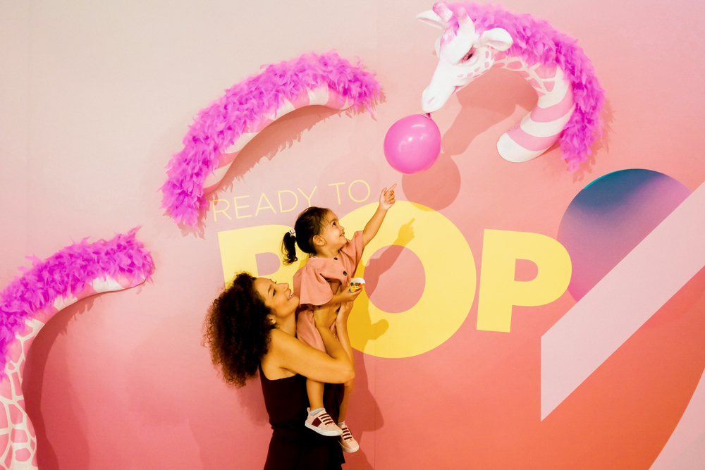 mother lifting up her young daughter as she reaches for a balloon hanging from a pink giraffe's mouth