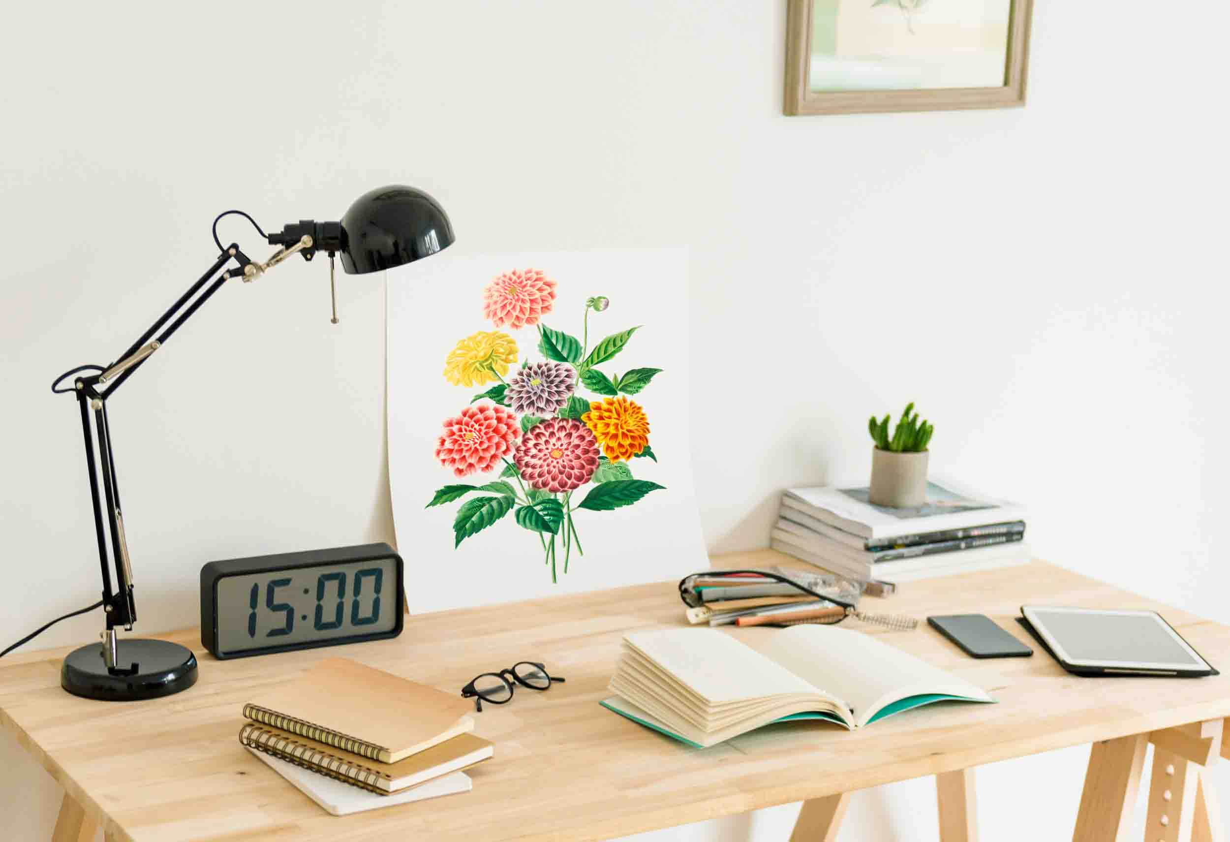 study desk with a lamp, digital clock, glasses, flower painting, and some notebooks