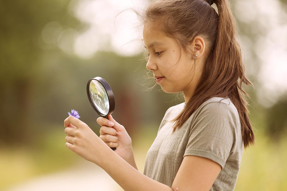 girl examining a microscope