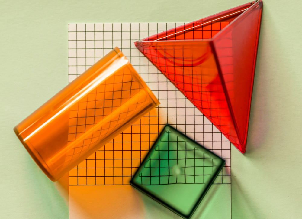 translucent cube, pyramid, and tube on top of a paper with grid lines