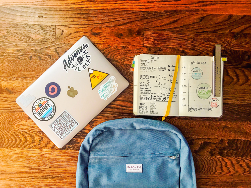 laptop with stickers, open notebook with notes, and a backpack on the floor