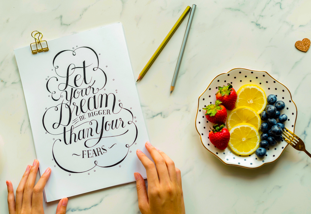 card laying on a table with the print 'Let your dreams be more than your fears' beside a plate with fruits