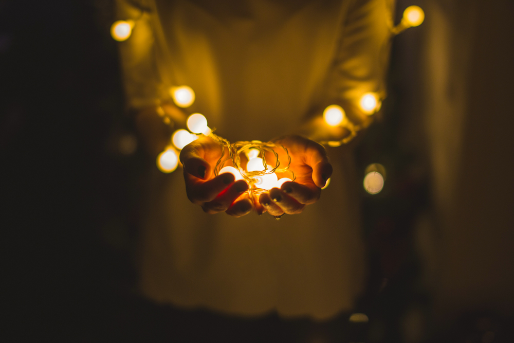 two hands holding out a string of glowing christmas lights