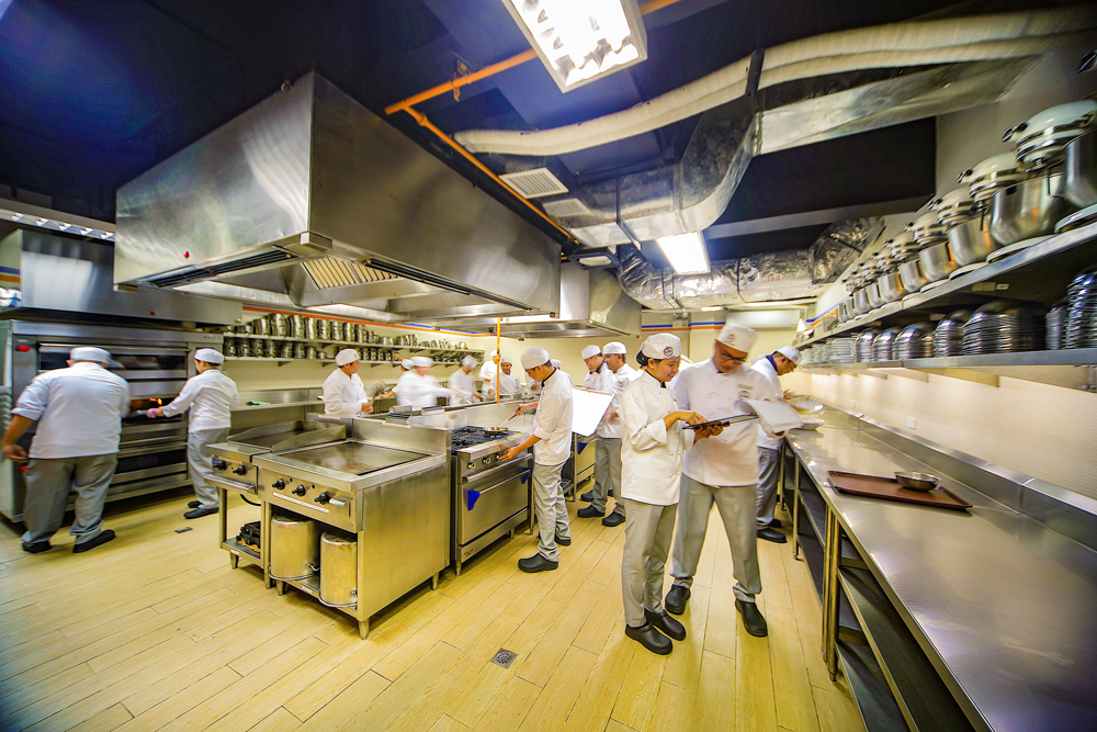 culinary students cooking and moving working together in a wide kitchen
