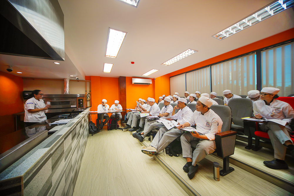 culinary students taking down notes while seated inside a classroom. Chef instructor speaking in front of the class