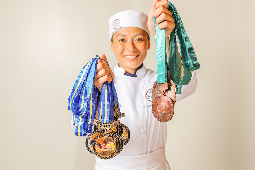 female chef smiling and holding up several medals in both hands