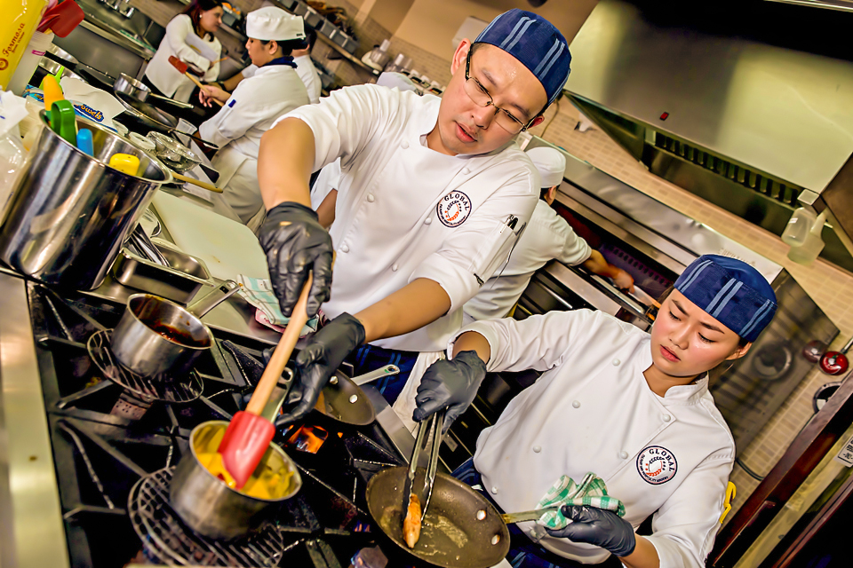 male and female chefs intently stirring food in pans