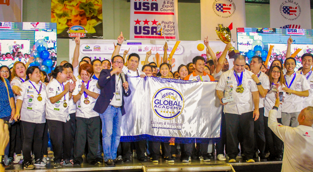 large group of people, many in chef's attire, holding up Global Academy banner, wearing medals, raising a trophy, and holding up their hands