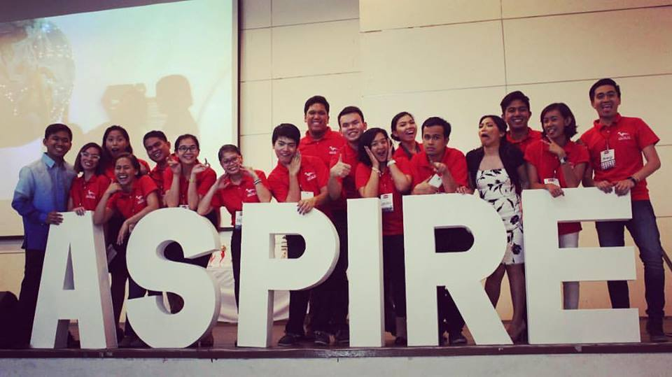"group of people in red t-shirts standing behind giant letters that spell ""ASPIRE"""