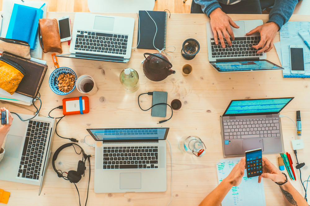 Overhead shot of hands working on laptops. Gadgets and headphones scattered across the table