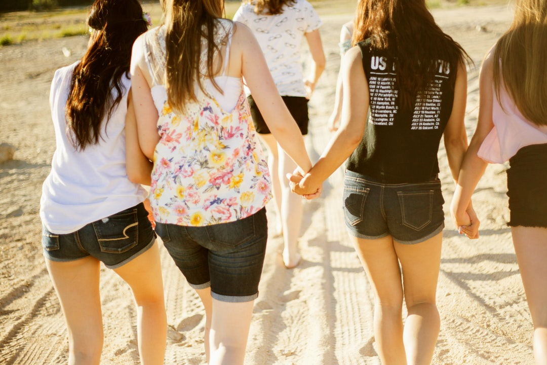 lady friends holding hands while walking