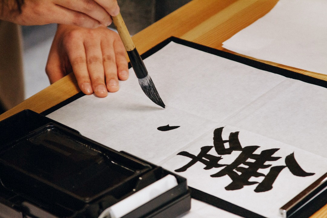 chinese characters being painted on a cloth