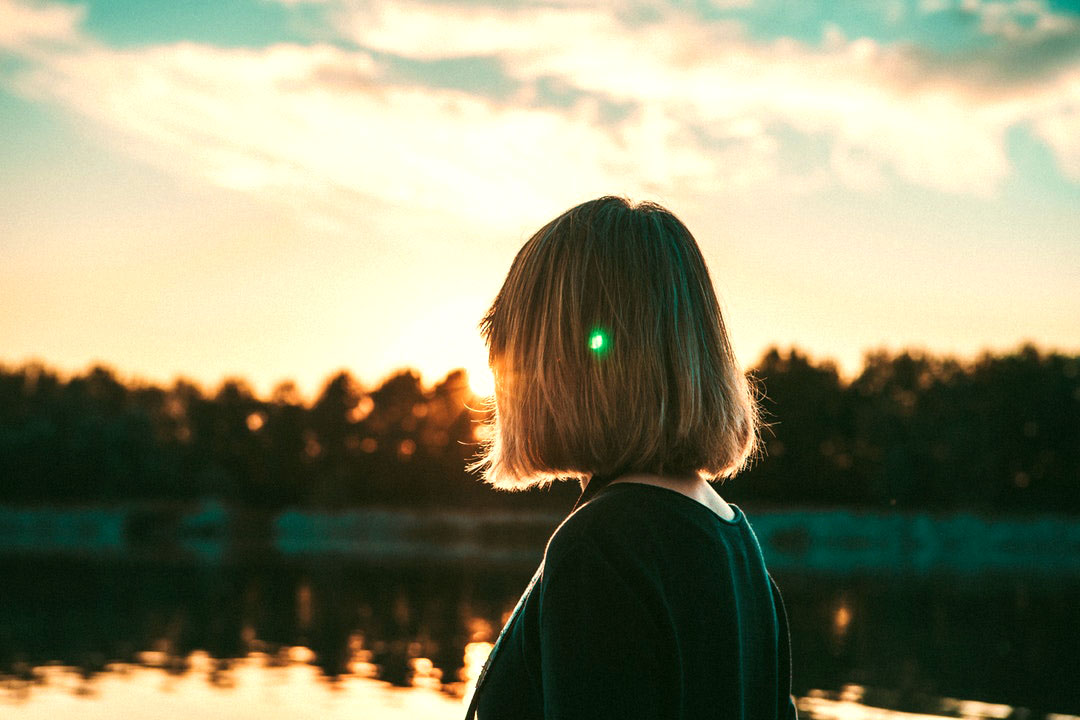 girl looking out onto a lake