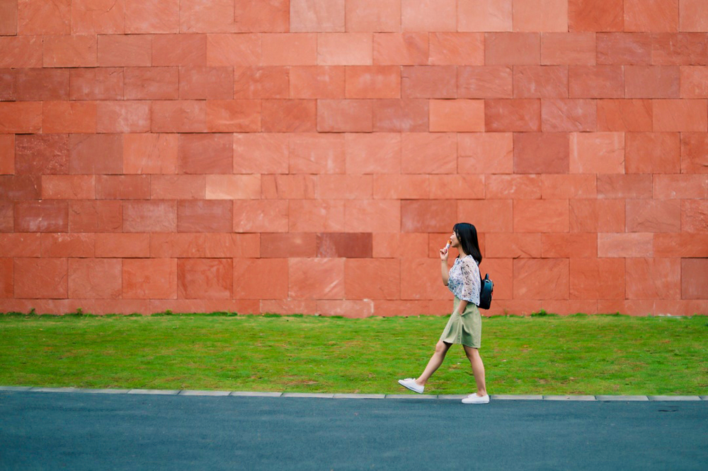 girl holding ice cream while standing in front of red brick wall
