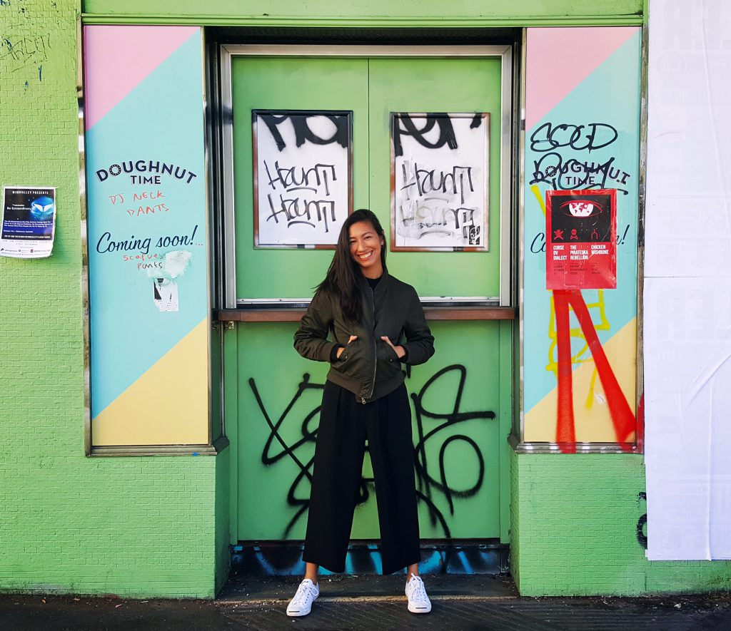 Jen Tarnate posing in front of a colorful door with graffiti