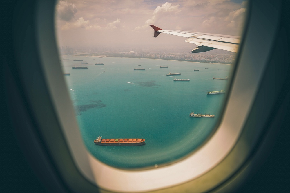 window plane with view of marine vessels