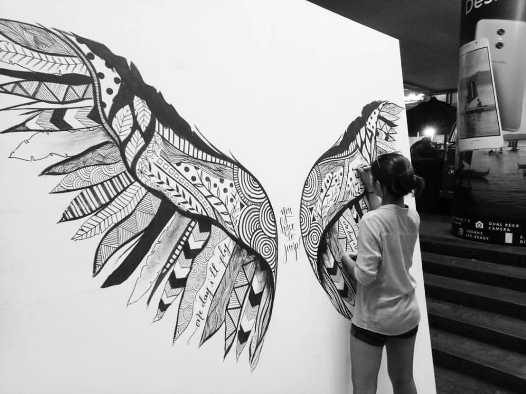 Details Ink founder Kara Pangilinan drawing a mural of wings