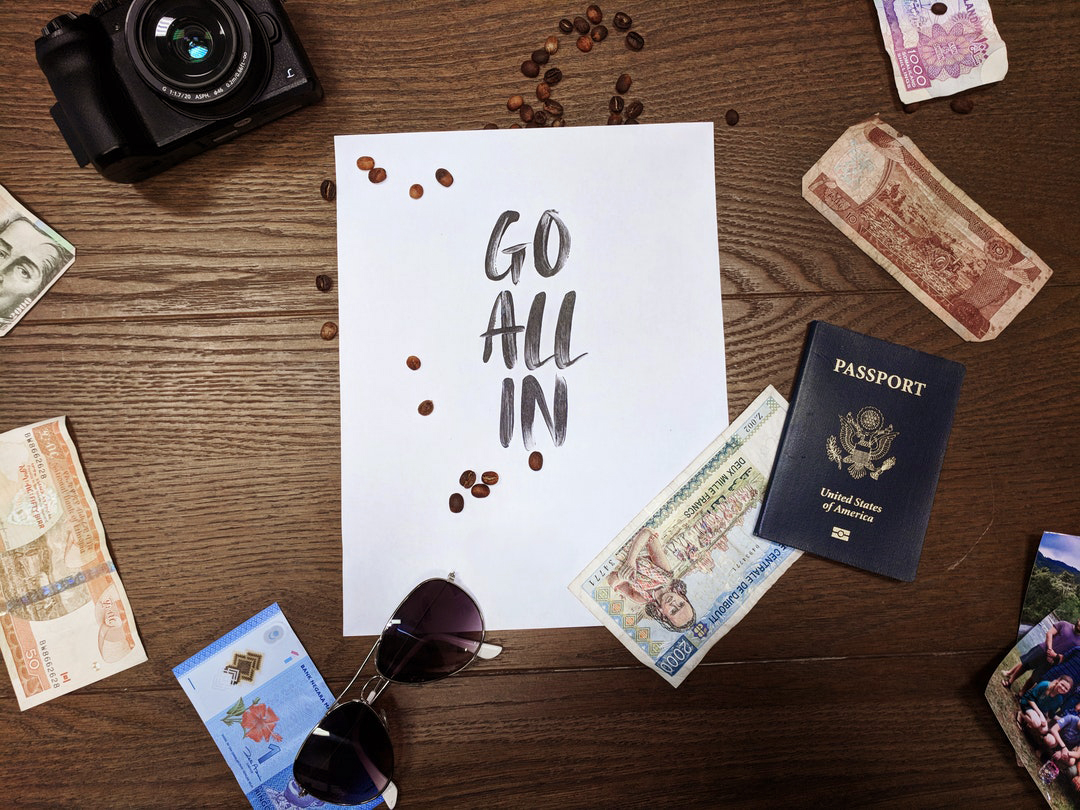 "USA passport and money scattered on a table, words ""go all in"" written on a paper"